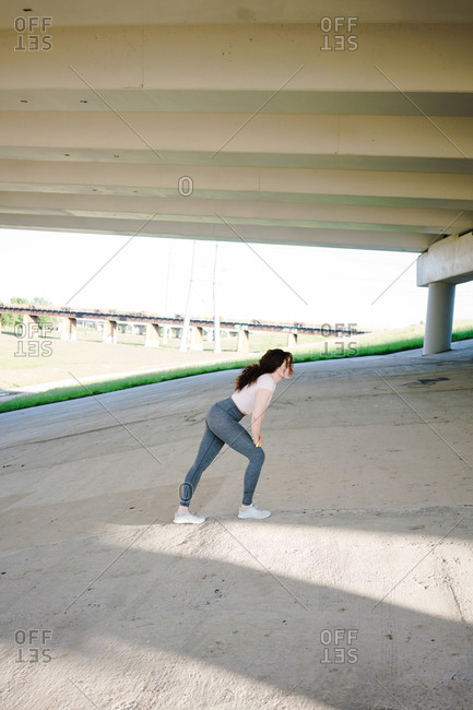 Young woman warming up on the slope under the bridge