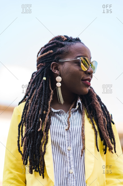 Side portrait of a young stylish girl with dreadlocks wearing reflective sunglasses