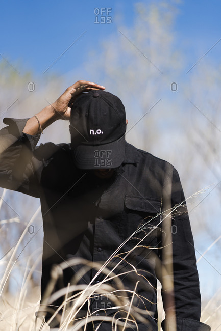 Portrait of a man walking in tall dry grass looking down and holding his cap
