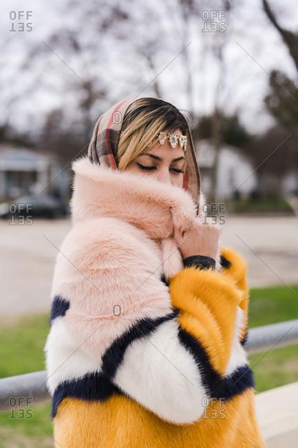 Shy Muslim woman posing in a fur coat hiding half of her beautiful face