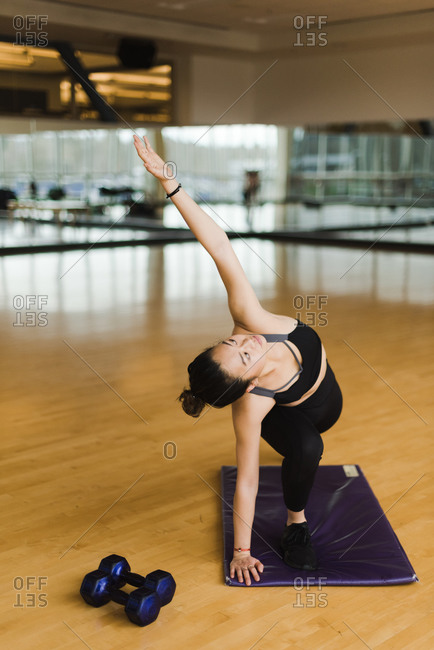 Vertical portrait of a young woman doing yoga in a studio on a yoga mat