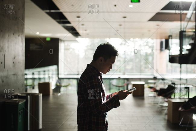 Close up of a man looking at his phone in office premises
