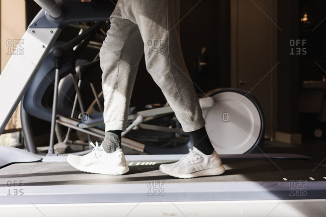 Wide shot of legs of a person walking on a treadmill