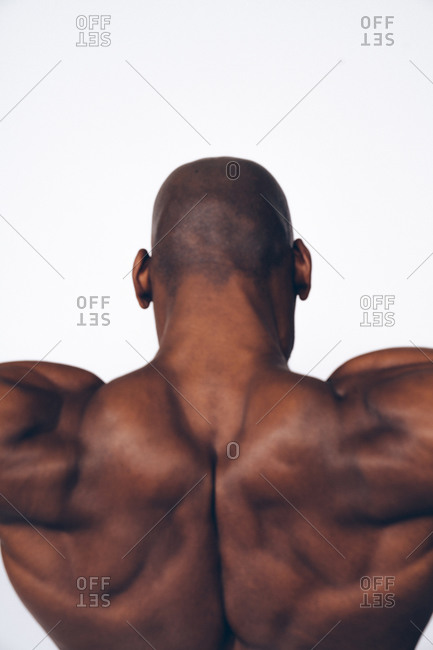 Vertical image of a muscular black man flexing his back muscles