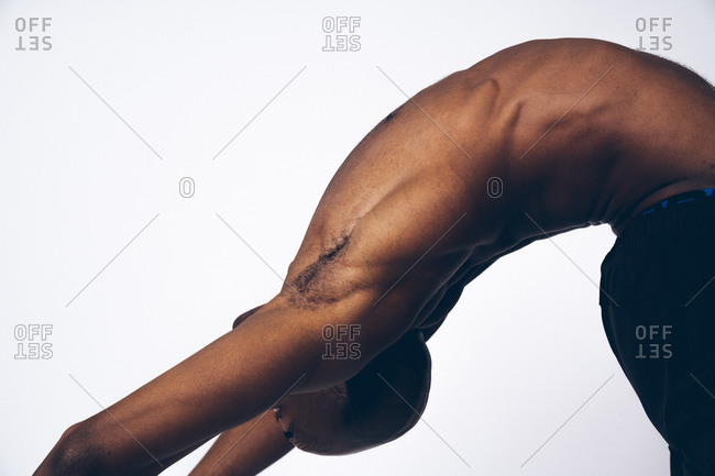 Topless muscular black man stretching his back muscles while performing yoga