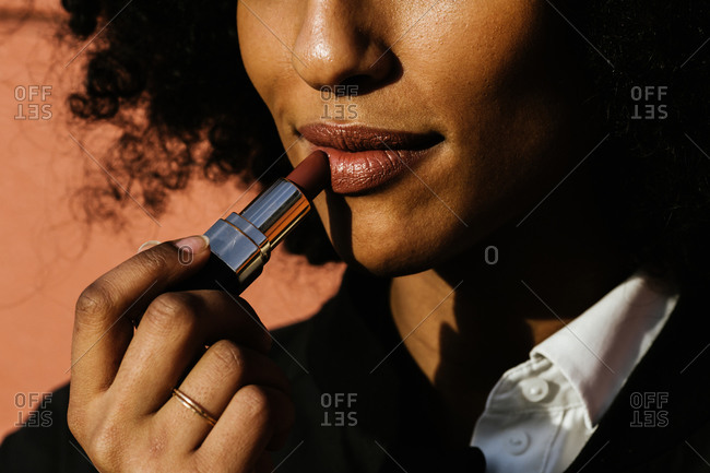 Close up of a woman with curly hair putting on lipstick