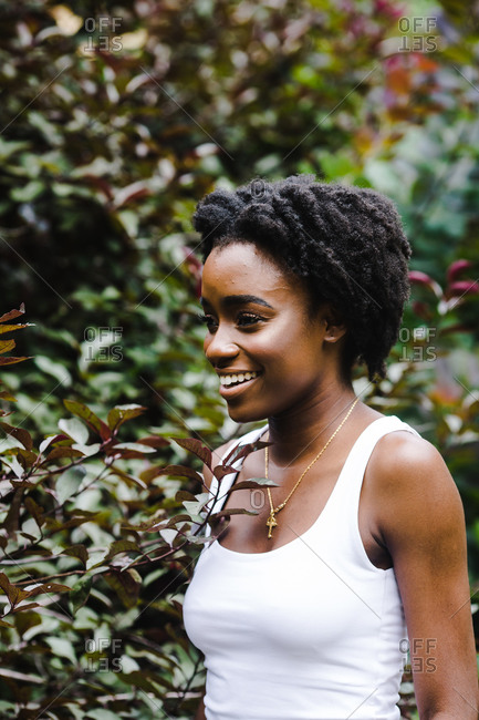 Portrait of a black woman smiling and standing next to a plant