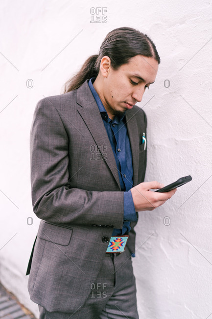 Three quarter length shot of a businessman leaning over a white wall checks his mobile phone