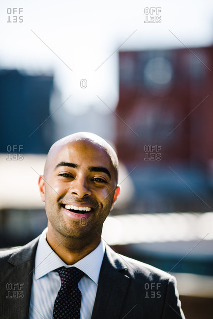 Portrait of a bald man in a suit and tie smiling at the camera