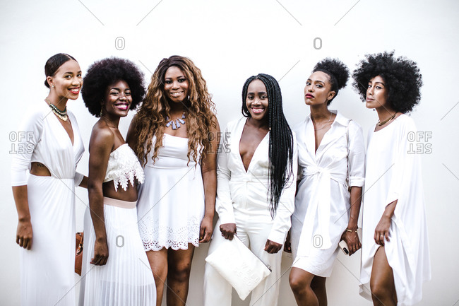 A group of black women wearing white attire pose in front of a white wall