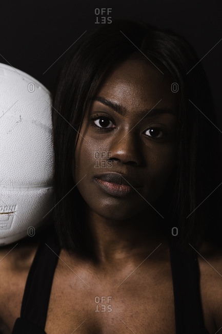 Close up portrait of a fitness model in sporty workout clothes holding a ball over her shoulder