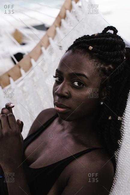 Black woman resting against a white hammock