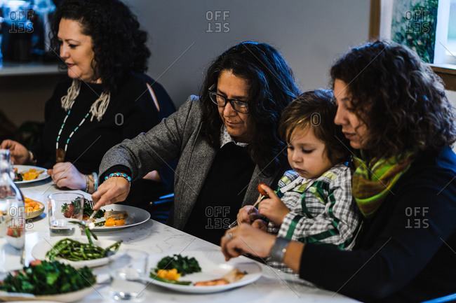 Horizontal shot of seated native american women dishing out food at a family meal