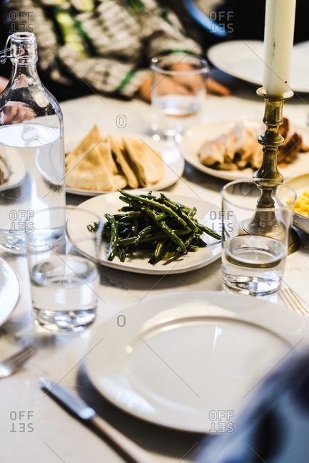 Vertical shot of plates with various delicacies set out on table at a dinner party