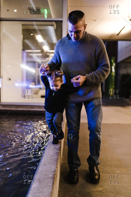 Vertical portrait of a father supporting his young daughter walk along the boundary of a water fountain indoors