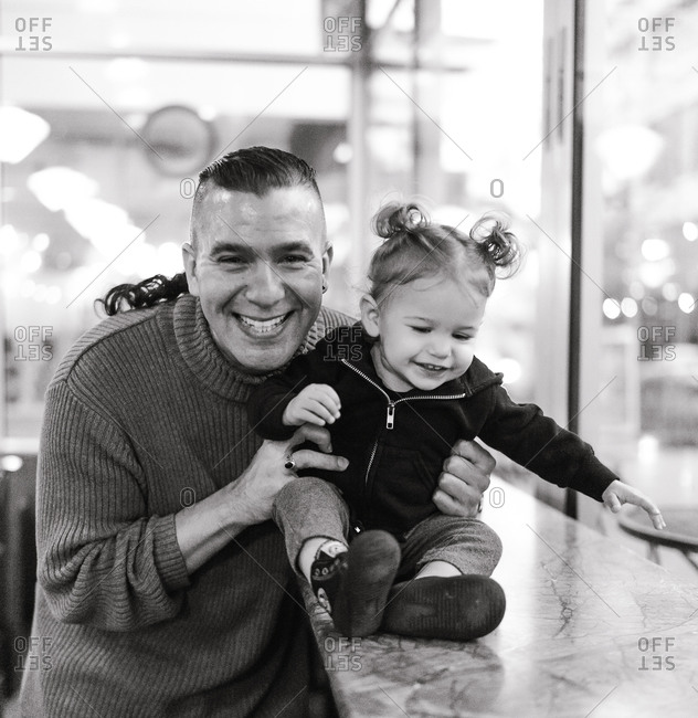 Black and white portrait of an American Indian and Alaska native father playing with his daughter over a table by the window