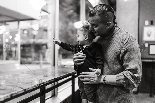 Black and white waist up shot of an American Indian and Alaska native father holding his daughter indoors looking outside