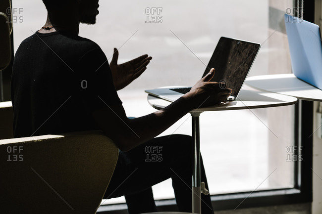 Side view of a man on his laptop looking at the screen
