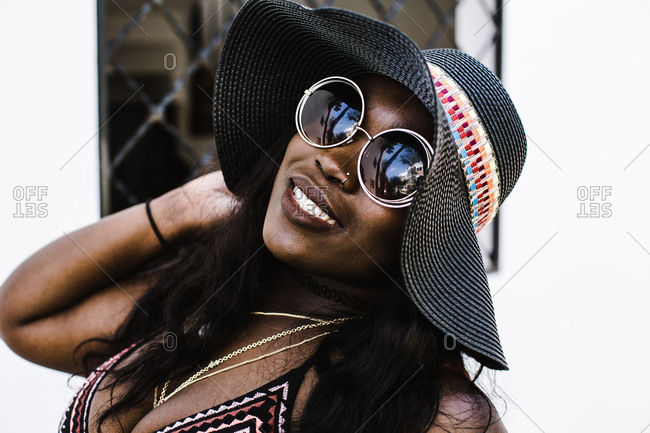 Woman with floppy hat and sunglasses smiling