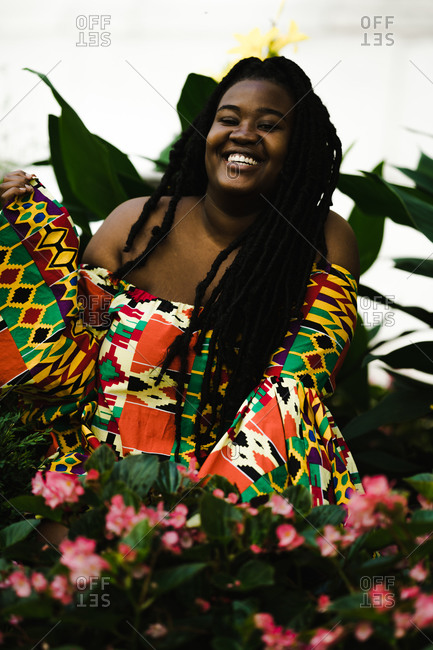 A portrait shot of a black woman in a colorful African dress with long braids laughing with flowers foreground