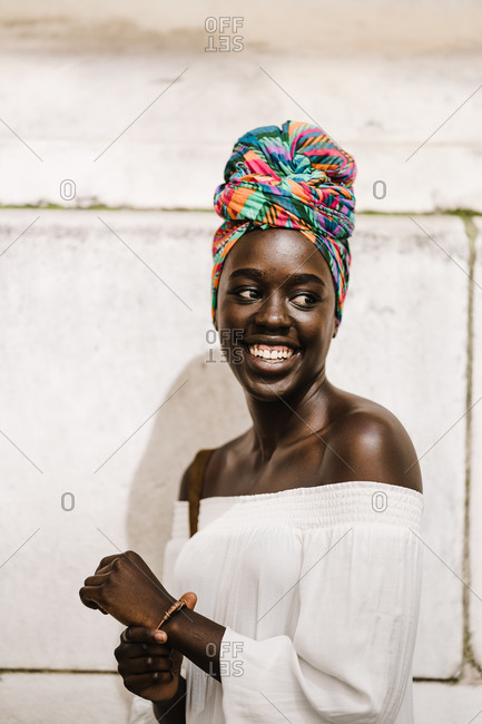 A portrait shot of smiling dark skin black woman in a white off-shoulder blouse standing against a wall