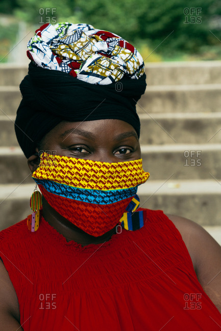 Close up of a black woman wearing a face mask and sitting on stairs in a park