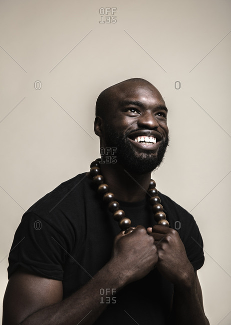 A close up shot of a happy bald African American man with beard posing with a big beads necklace while looking up