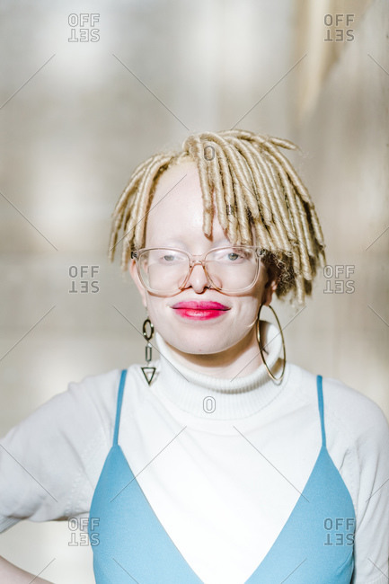 Vertical portrait of an albino woman standing by a wall smiles at the camera