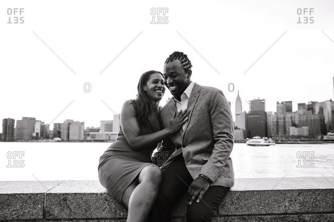 Horizontal shot of a young couple sharing a light moment sitting by a waterfront