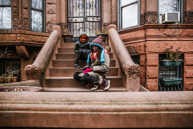 Wide shot of a black boy and girl sitting on a building's steps in winter clothing look at the camera