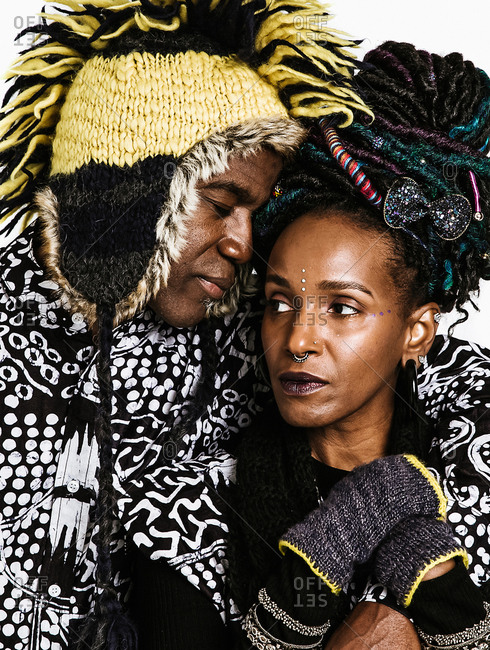 Black man wearing yellow and black hat embracing woman with piercings and colorful hair