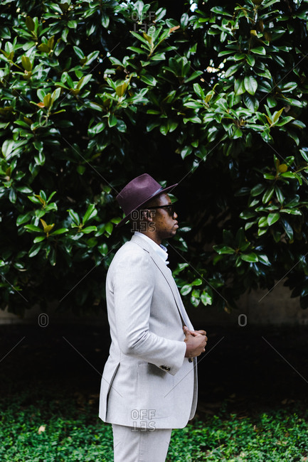 Man in a white suit and purple hat standing outside