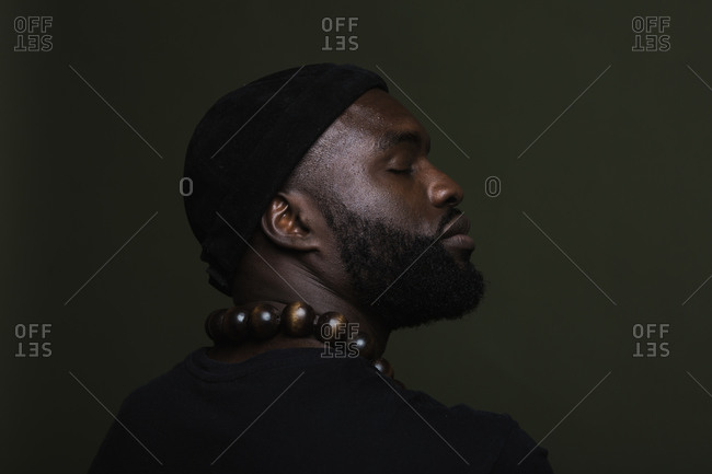 A close up back shot of a serious African American man wearing a black beanie cap and a big beads necklace posing against a green background with his eyes closed