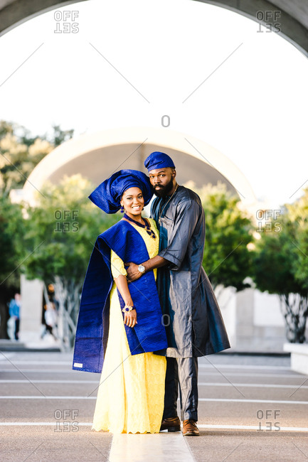 Vertical portrait of an african couple wearing traditional clothing embrace one another outdoors