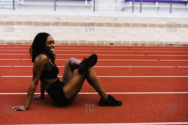 Horizontal shot of a sitting black female athlete laughing during practice on a track with copy space