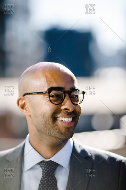 Close up of a smiling bald man in a suit and glasses