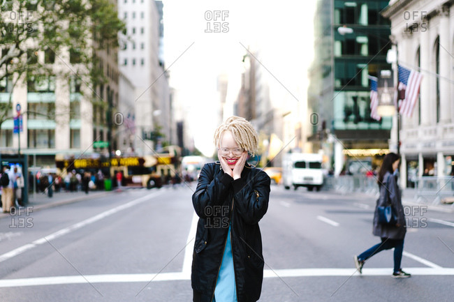 Horizontal shot of a joyous albino woman with hands on her cheek in the city street