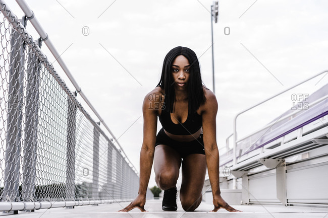 Horizontal shot of a black female athlete on mark on a race track looking at the camera