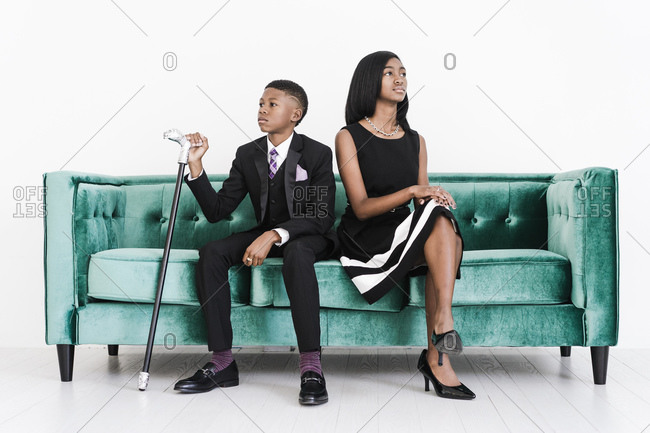 Two young black children dressed in formal outfits sit on a green velvet couch