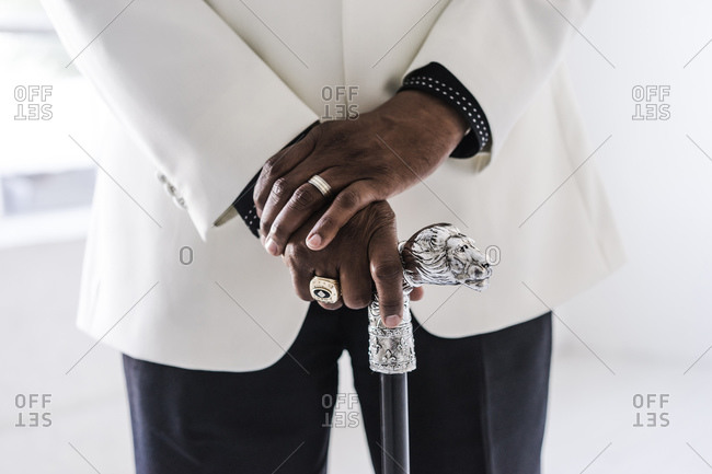 Horizontal shot of mid section of a man holding a fancy cane in a white suit
