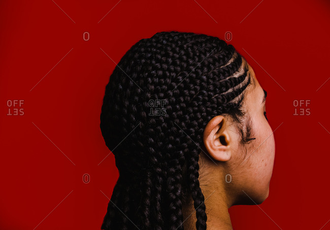 Woman with long braids in front of a red wall