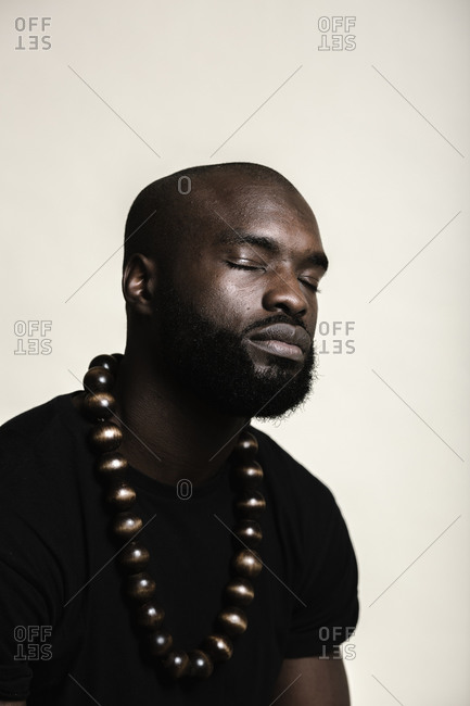 A close up shot of a bald African American man with beard posing with his eyes closed wearing a big beads necklace