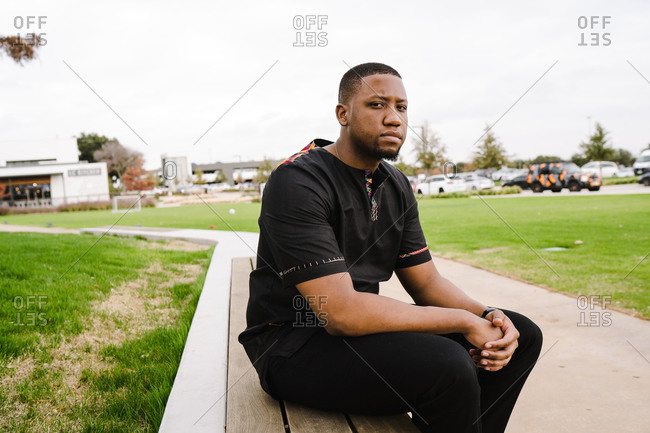 Black man in black leisure wear sitting in a park with arms crossed over each other and looking confidently at the camera