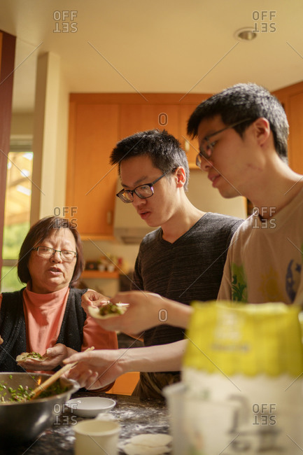 Taiwanese mother making chicken dumplings in the kitchen along with her two adult sons