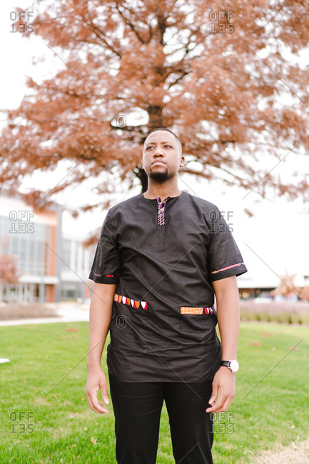 Confident black man in stylish black clothes standing in the park