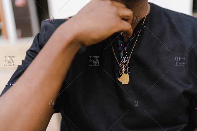 Close up of a black man fixing his t-shirt collar buttons