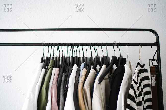 Front view of a clothes rack with pastel colored shirts and t-shirts hanging on it