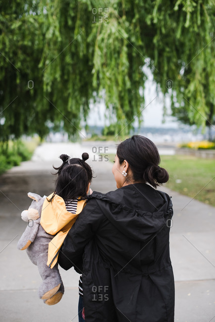 Mother holding her daughter in her arms and walking on an empty street