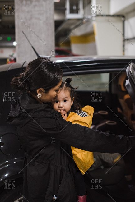 Mother with her daughter in her arms standing beside a car holding its door