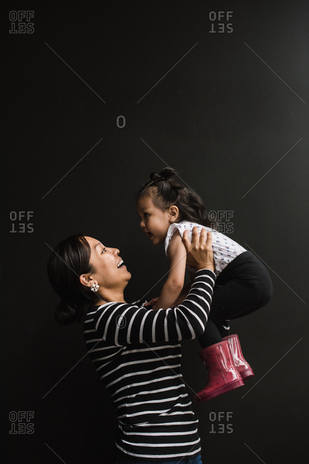Vertical shot of a mother holding her daughter up in the air against a black background